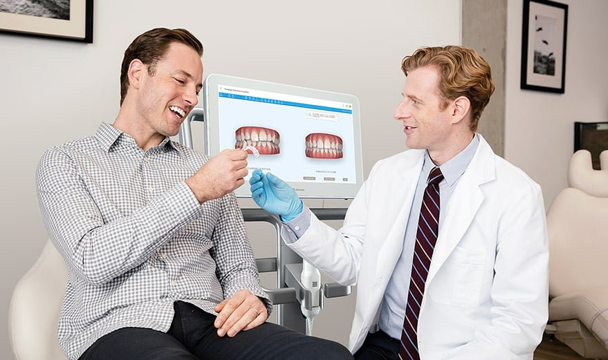 doctor handing over Invisalign aligners to patient